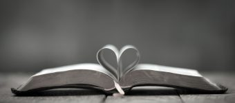 Bible on the table with heart shaped pages.